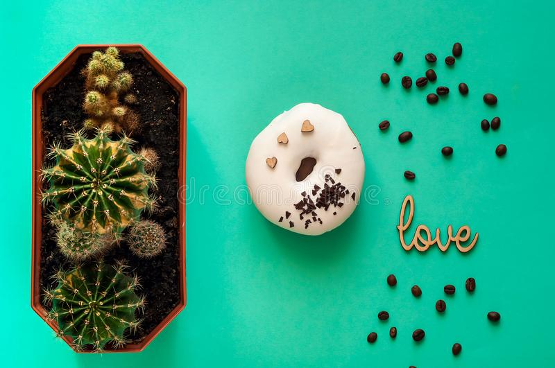 White glazed donut with black chocolate sweets with small cactuses.Food creative concept. TGreen Neon Mood on mint background royalty free stock photo