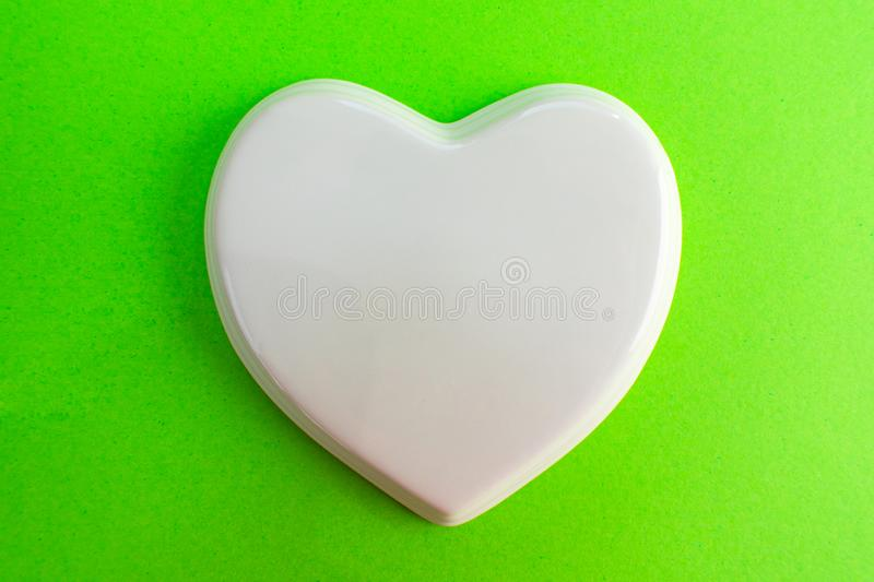 White glossy porcelain heart to a green  violet background; wedding; Wedding card; Love note. White glossy porcelain heart to a green background; wedding stock photos