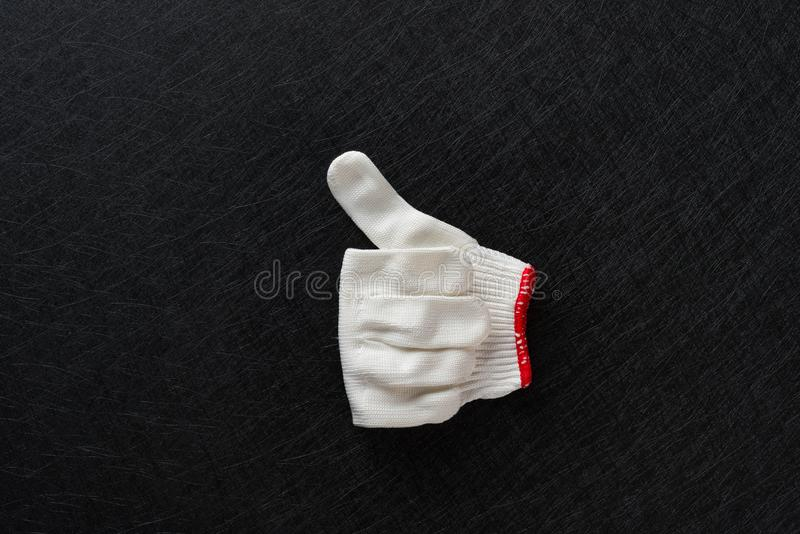 White glove with gesture of thumbs up on balck. Background stock image