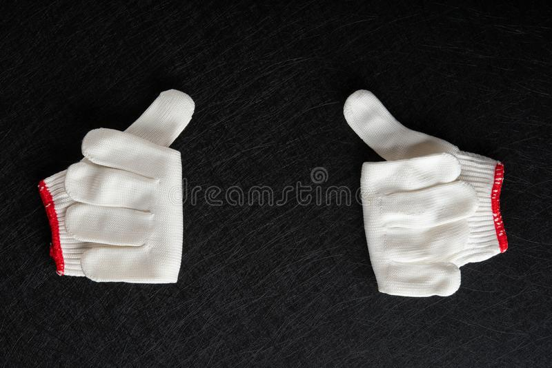 White glove with gesture of thumbs up on balck. Background stock photos