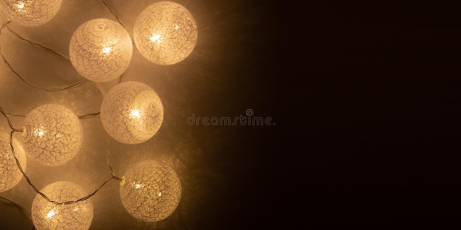 White glowing balls. home decoration for a holiday with a glowing garland. On black background stock photos