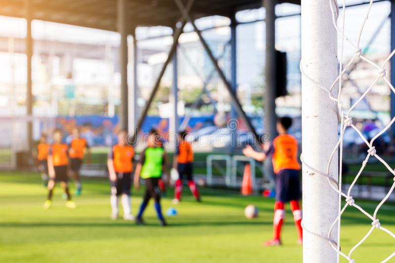 White goalposts and mesh of goal with blurry football players. stock images