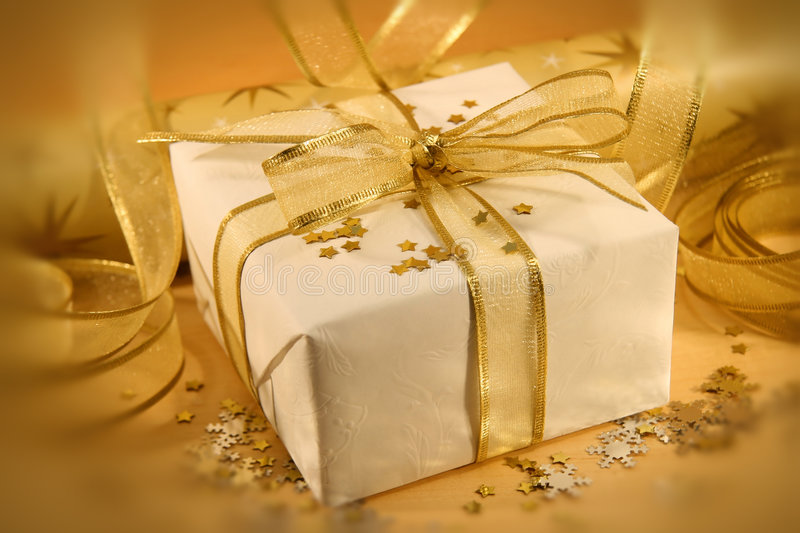 White and gold. Christmas gift wrapped with white and gold paper and bow royalty free stock photo