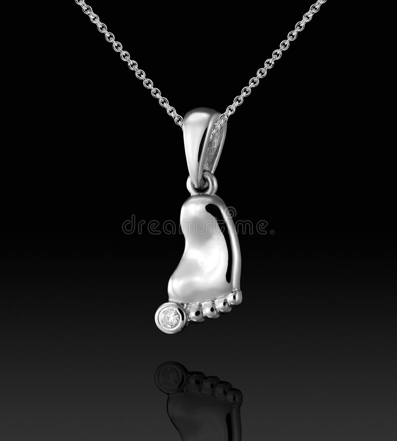 White gold child`s footprint pendant with diamond on black background royalty free stock images
