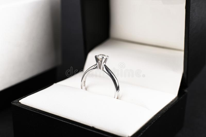 White gold diamond engagement ring, platinum boxed on white background. Wedding, offer as a gift for Valentine`s Day. White gold diamond engagement ring stock images