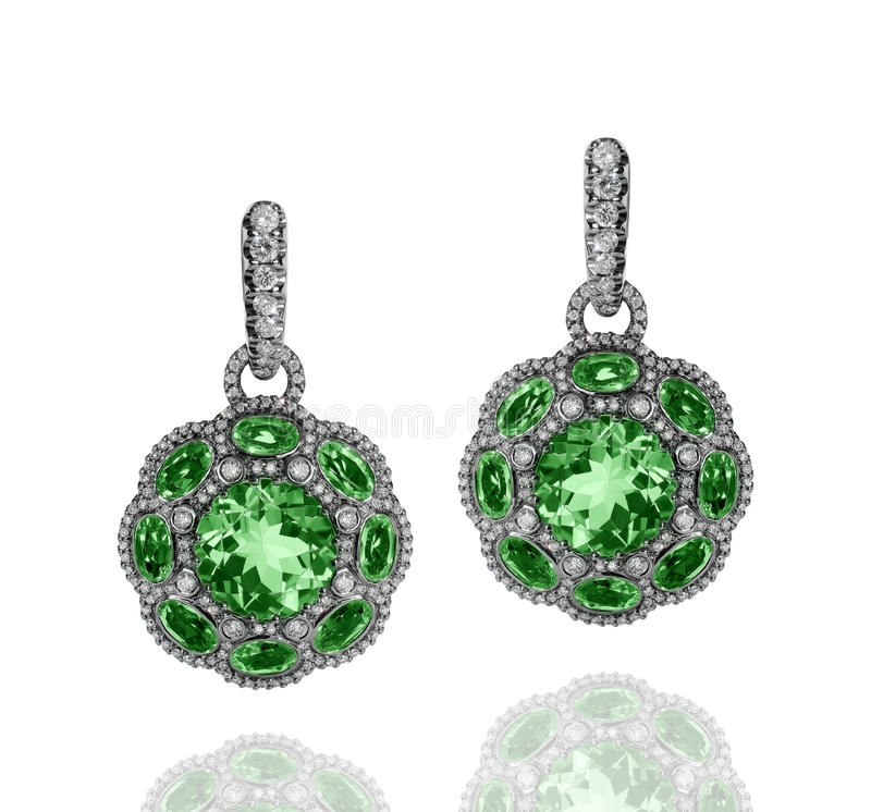 White gold earrings with green emeralds and white diamonds royalty free stock images