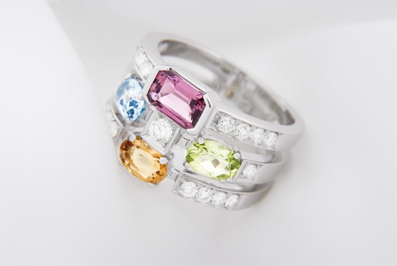 White gold ring with citrine peridot, blue topaz, pink tourmaline and diamonds on soft white stock images