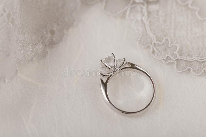 White gold wedding ring with diamonds on white background with l. Ace. Silver engagement ring. Nuptials lifestyle. Copy space royalty free stock photos