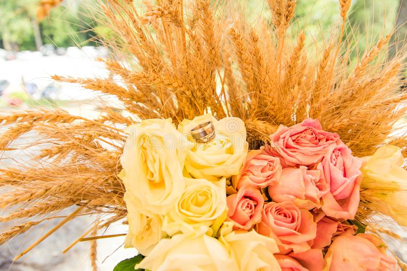 Wedding Rings on Roses Bouquet and Wheat Ears stock photos
