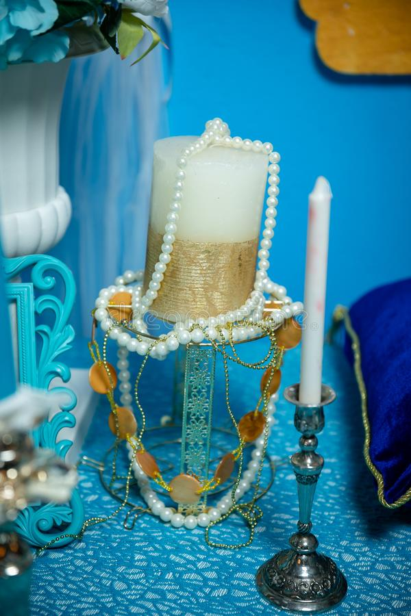 White-Golden candle wrapped with pearl beads on a glass candlestick. White candle in a silver candlestick. On the background of a stock photos