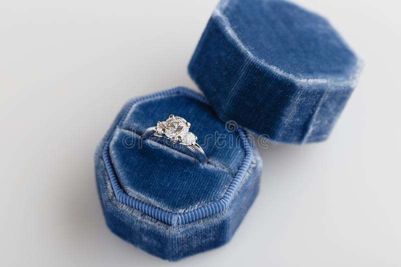 White golden wedding ring with diamonds in blue vintage velvet r. Ing box on white background. Silver engagement ring lifestyle stock photos