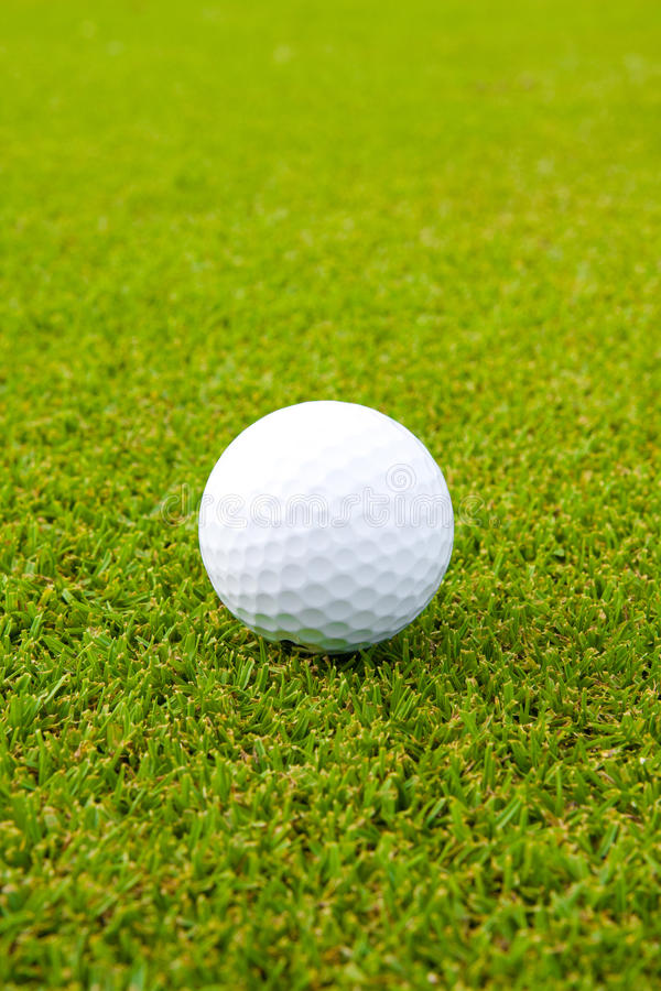 White golf ball on green stock photography
