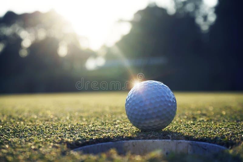 White golf ball near hole on green grass stock photos