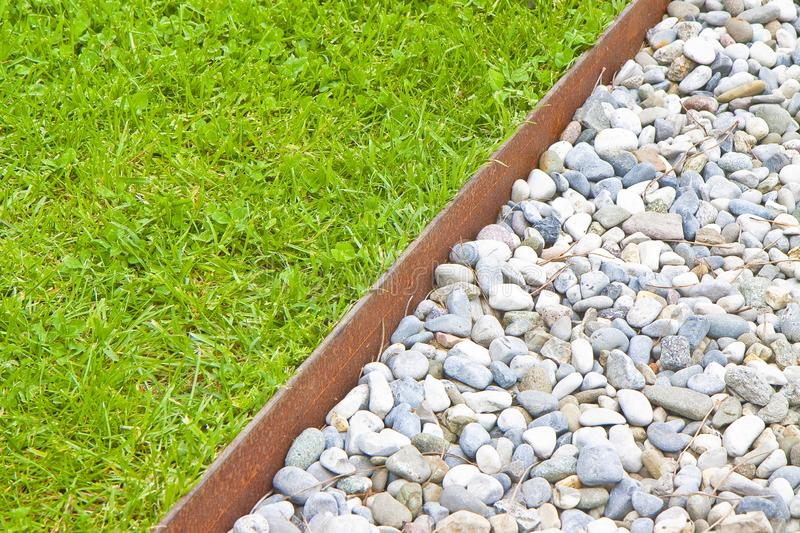 White gravel floor and fresh green lawn with clovers and rusty metal containment profiles royalty free stock image