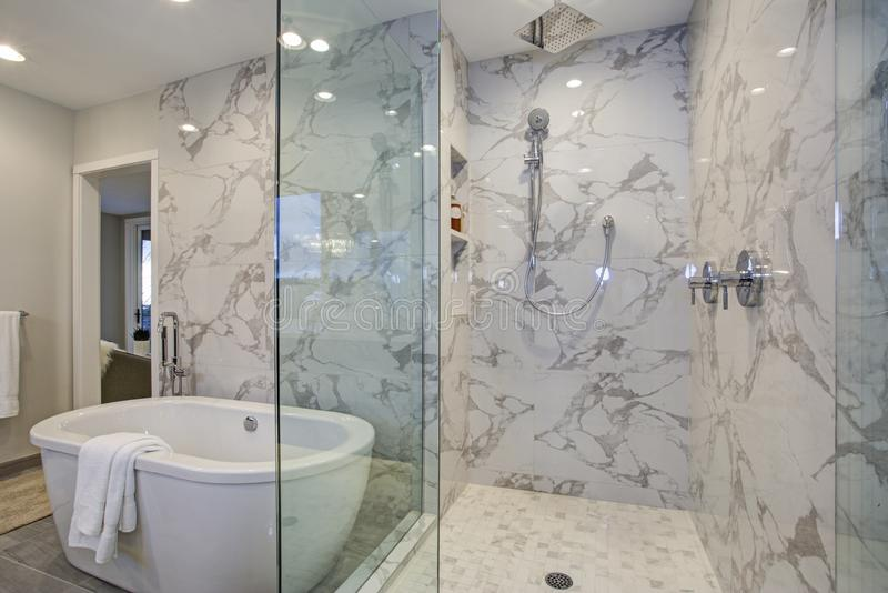 White and gray calcutta marble bathroom design. With custom soaking tub and glass walk in shower stock photos