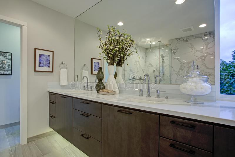 White and gray calcutta marble bathroom design. With quartz counters, floating cabinets and large mirror royalty free stock photo