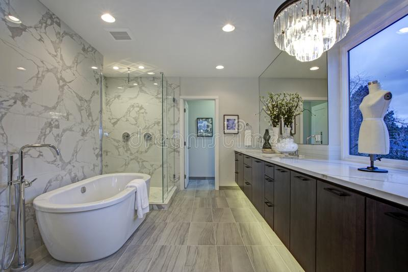 White and gray calcutta marble bathroom design. With tiled floors, quartz counters, floating cabinets and freestanding tub stock photos