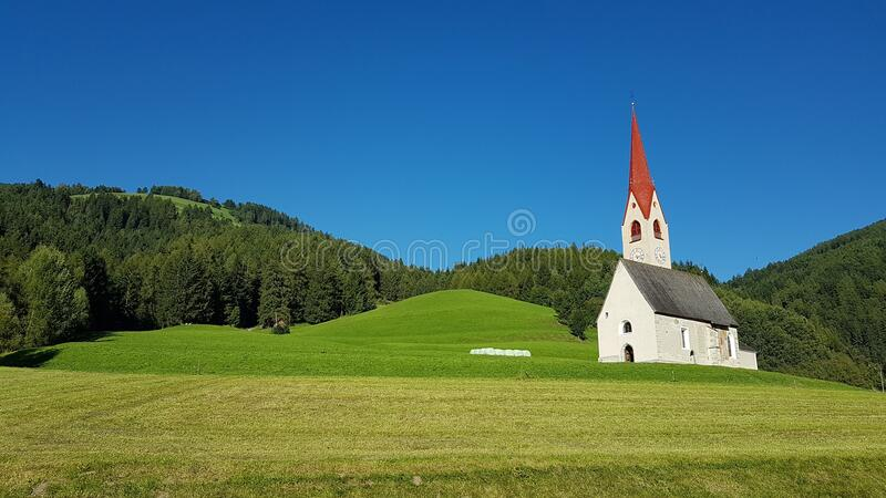 White Gray and Red Chapel on Green Field during Clear Sky Day Time royalty free stock photos