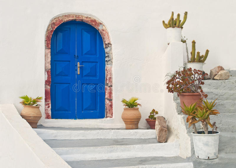 White Greek house facade with blue door and flower pots stock photography