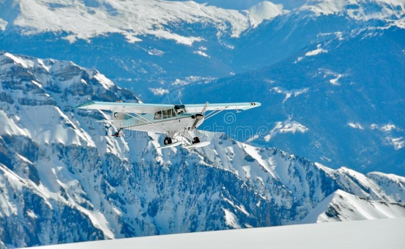 White and Green Monoplane Flying Above Mountains stock images