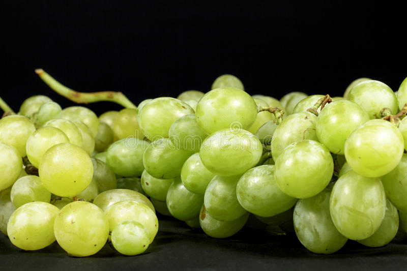 White and green table grapes isolated on black background royalty free stock images