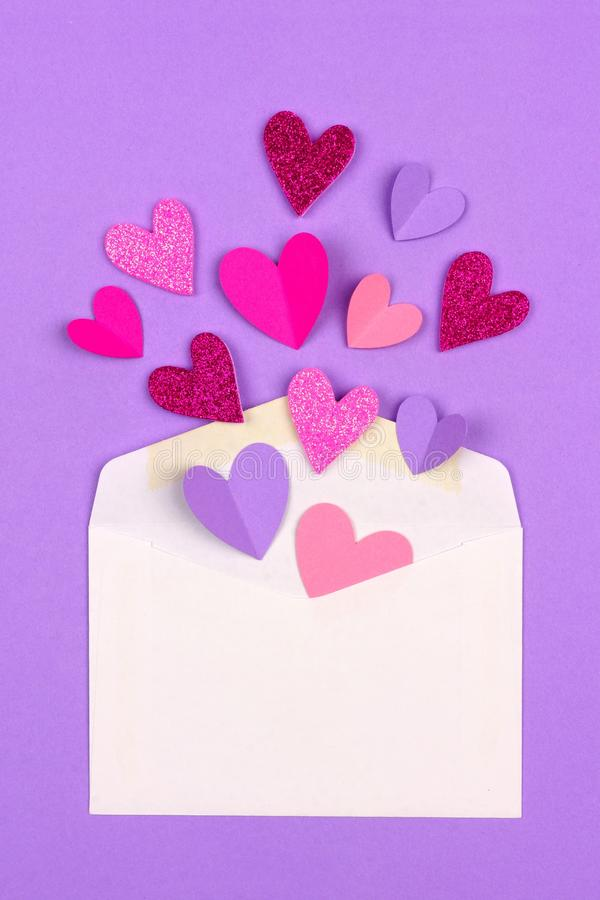 White greeting card envelope with hearts flying out royalty free stock images