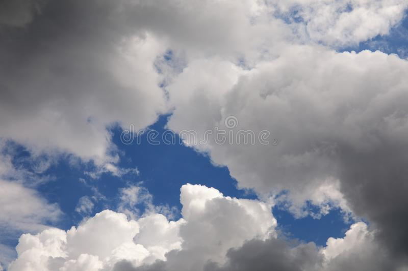 White and grey clouds on the sky background, cloudy weather with sunlight. White and grey clouds in the blue sky background, cloudy weather with sunlight royalty free stock image