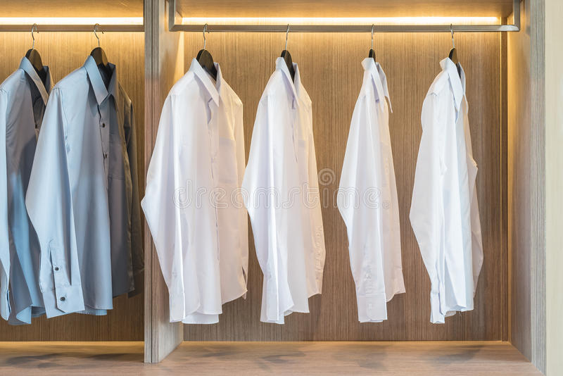White and grey shirts hanging in wardrobe. White and grey shirts hanging in wooden wardrobe stock images