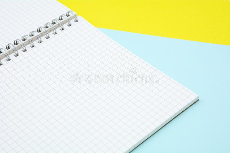 White grid paper book on blue and yellow paper. stock photo