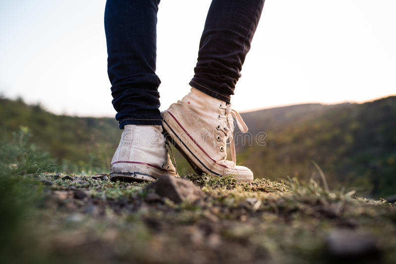 The white grunge shoes on the rock in park. Beautiful spring background with blurred background. Low depth of field. Detail of woman's legs royalty free stock photos