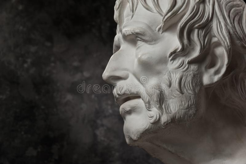 Gypsum copy of ancient statue Seneca head on dark textured background. Plaster sculpture man face. White gypsum copy of ancient statue of Lucius Seneca head for stock image