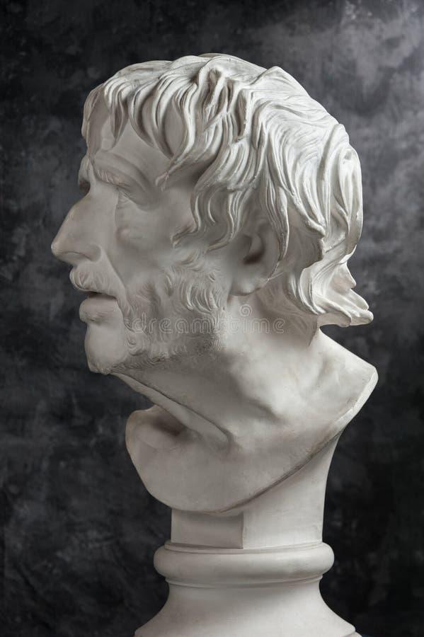 Gypsum copy of ancient statue Seneca head on dark textured background. Plaster sculpture man face. White gypsum copy of ancient statue of Lucius Seneca head for stock images