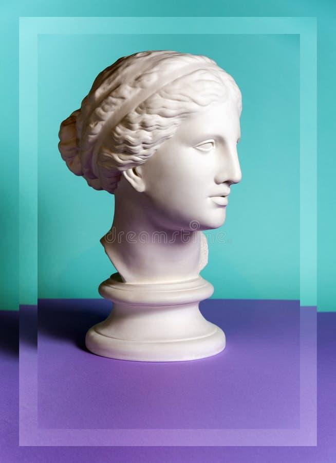 White gypsum copy of ancient statue Venus head on a green purple background. Plaster sculpture woman face. White gypsum copy of ancient statue of Venus de Milo royalty free stock image
