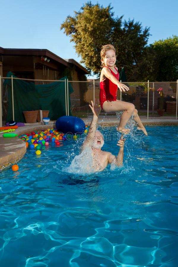 White Haired Grandfather Throws His Granddaughter in the Swimming Pool the Girl has a Big Smile on her Face as She Flies Through stock photos