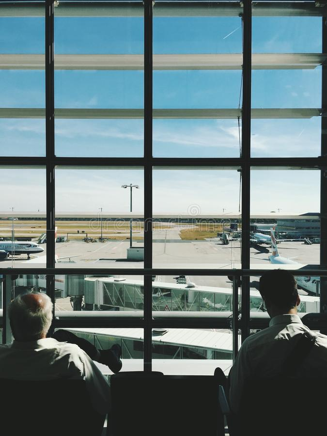 White Haired Man Seating Beside Person In Gray Dress Shirt In Front Of White And Black Framed Window Near White And Blue Air Plane Free Public Domain Cc0 Image