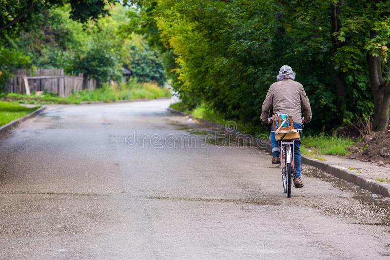 White haired old man riding bicycle on roadside after rain at summer royalty free stock photo