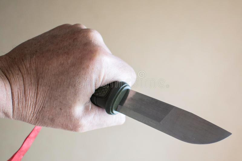 White hand with knife pointing to the right. Image of a white Caucasian fist holding a knife with an green hilt pointing the blade to the right ready to stab or stock photography