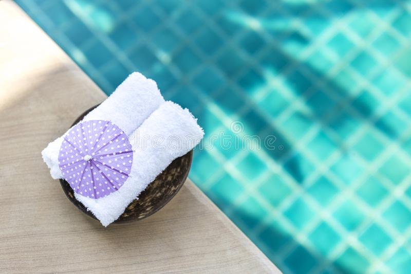 White hand towel with purple paper umbrella on swimming pool edge with space on blurred blue water background royalty free stock photography