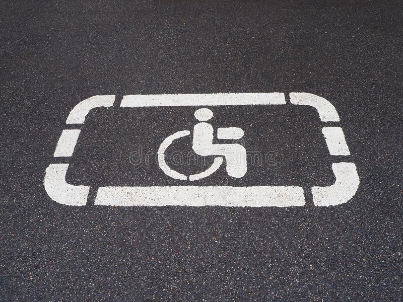 White handicapped symbol of wheelchair painted on asphalt on a parking lot, sign of parking space for disabled visitors stock image