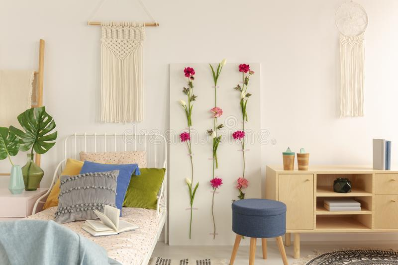 White macrame above single metal bed with colorful pillows and doted bedding in fashionable boho bedroom interior. White handmade macrame above single metal bed royalty free stock photos