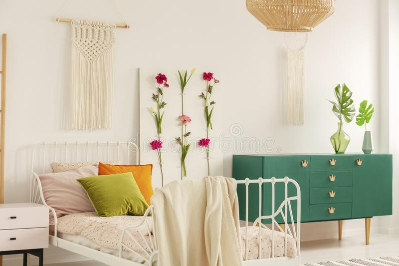 White handmade macrame above single metal bed with colorful pillows and doted bedding in fashionable boho bedroom interior with. Green cabinet and floral board stock photo
