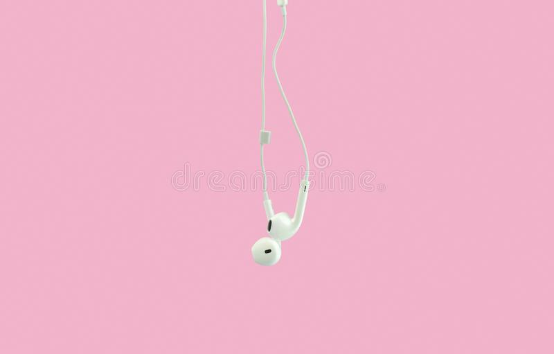 White hanging ear buds headphones isolated on a pink background. White hanging ear buds headphones isolated on a pink stock image