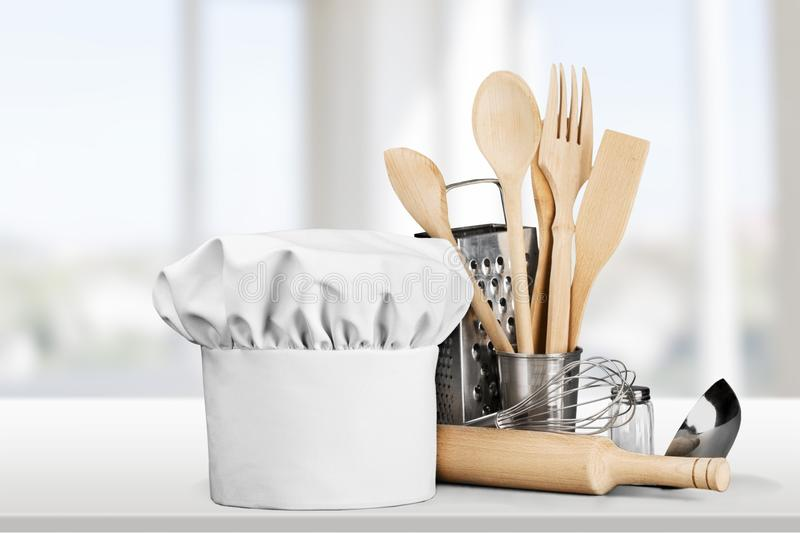 White chef hat and utensils on table royalty free stock photography