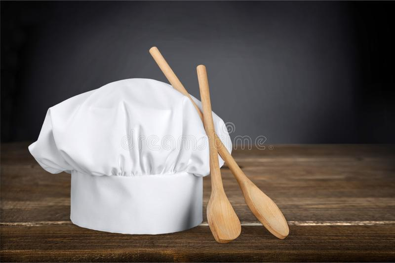 White chef hat and wooden spoons stock images
