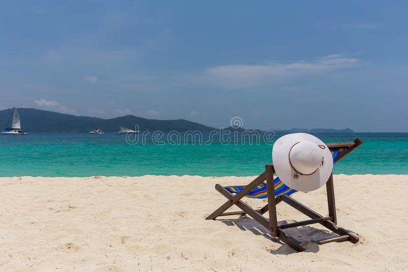 The white hat lies on the edge of the chaise longue, the seashore with a beautiful view. stock photo