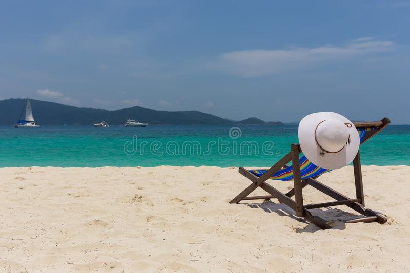 The white hat lies on the edge of the chaise longue, the seashore with a beautiful view. royalty free stock images