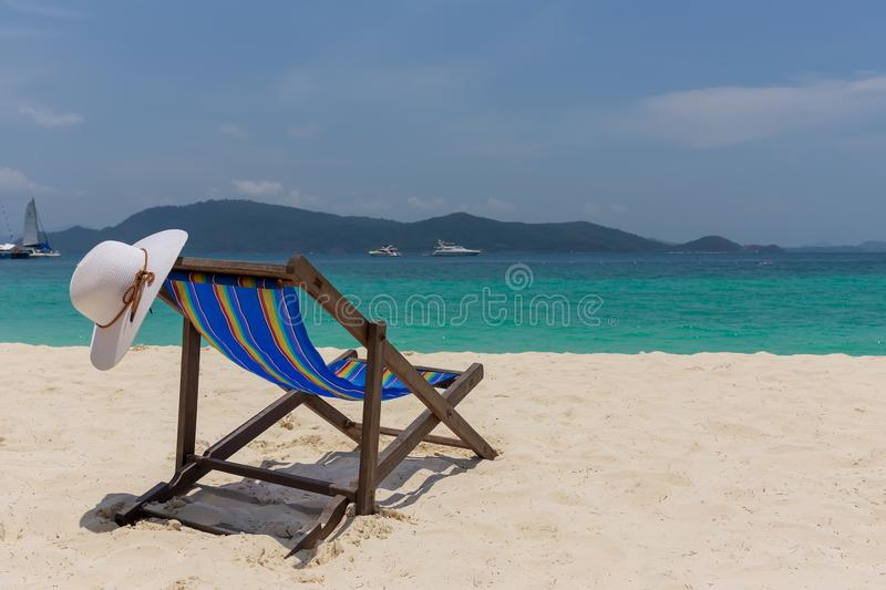 The white hat lies on the edge of the chaise longue, the seashore with a beautiful view. royalty free stock image