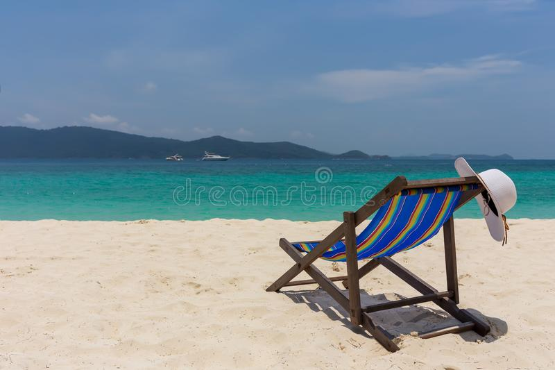 The white hat lies on the edge of the chaise longue, the seashore with a beautiful view. royalty free stock photography