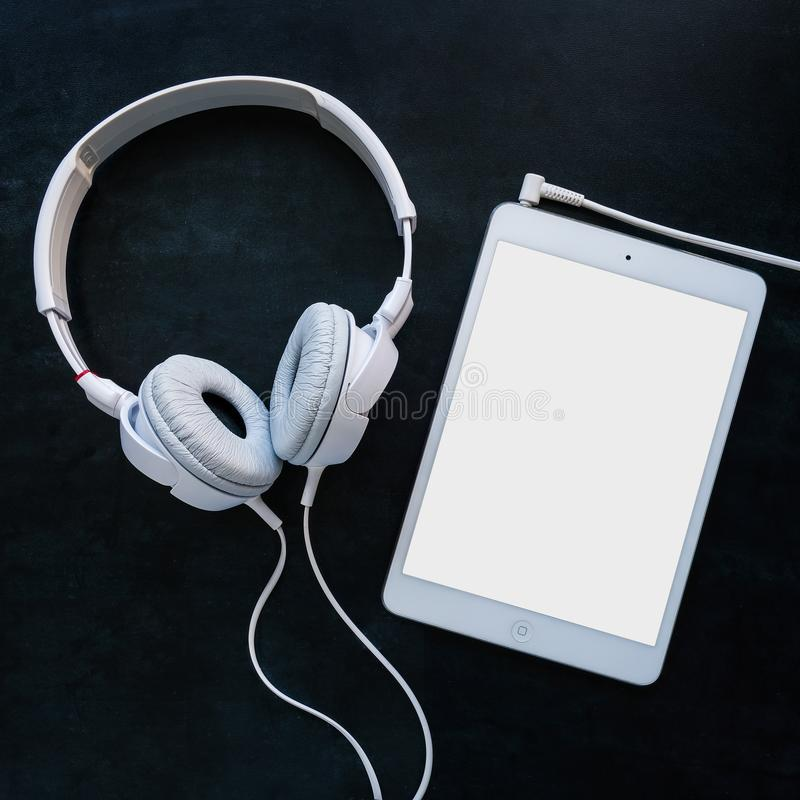 Headphones with cable on a black table royalty free stock images