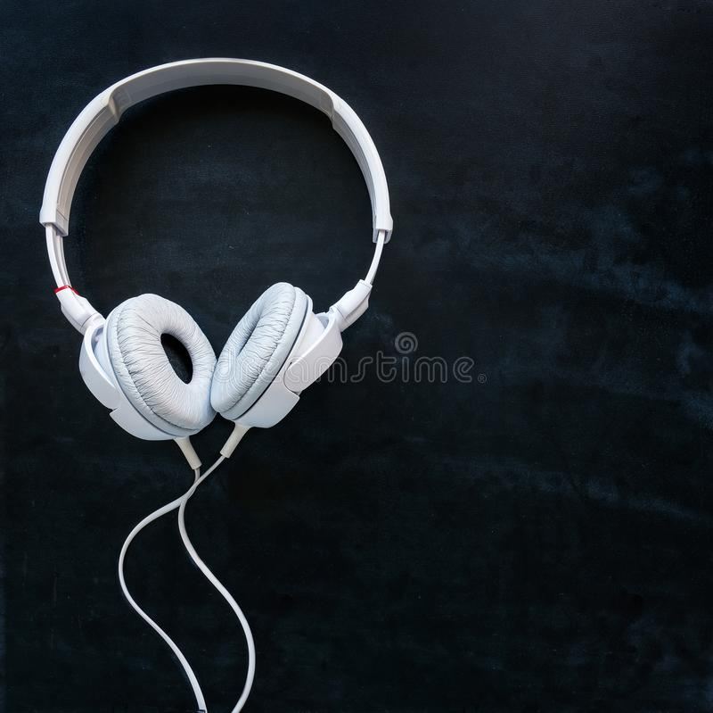 Headphones with cable on a black table royalty free stock photography